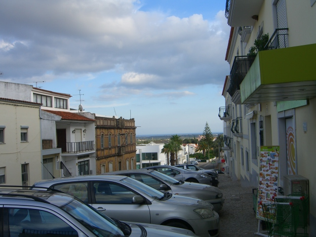 Grey cars, buildings old and new, sea in the distance.